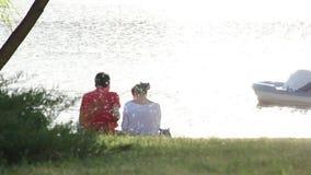 Die Paare, die zusammen auf dem Strand nahe den Palmen sitzen, sprechen, beruhigen stock video