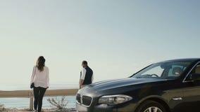 Die Paare gehen vom Auto hinaus und kommen zum Abgrund, den Ozean zu genießen stock video footage
