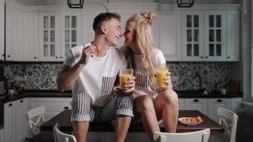 Die Paare küssen, die Spaß während des Frühstücks haben stock footage