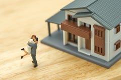 Die Paarminiatur2 menschen, die mit Hausmodell vorbildlich stehen, machen Familie Fühlung glücklich als Immobilien des Hintergrun Stockfoto