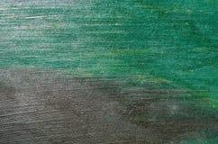 Die Pappe wird mit einer Aquarellfarbe von grünen und schwarzen Farben bedeckt Lizenzfreie Stockfotografie
