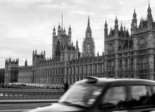 Die Parlamentsgebäude mit dem Taxi, das in Front überschreitet Lizenzfreie Stockbilder