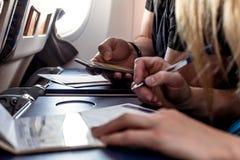 Die Passagiere, die Immigration ausfüllen, bildet sich in den Flugzeugen stockfotografie