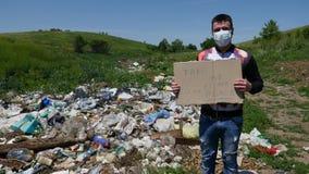 Die Person in der Maske auf dem Abfall hält ein Zeichen mit dem Text Lizenzfreie Stockbilder