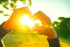 Die Person, die Herz mit macht, überreicht Natursonnenunterganghintergrund Lizenzfreies Stockfoto
