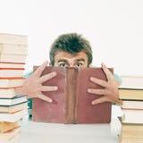 Die Person versteckt das Gesicht hinter dem alten Buch. Lizenzfreie Stockfotos