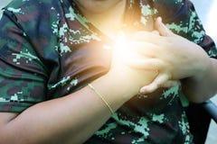 Die Person, welche die Militäruniform trägt, nahm seine Hand zum Kasten, der passend ist, im Herzen zu schmerzen stockbild