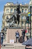 Die Pferdezahmere Statue auf Anichkov-Brücke und den Leuten über sie an einem klaren Frühlingstag Stockbild