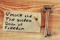 Die Phrase - entriegeln Sie die goldene Tür der Freiheit geschrieben auf die Anmerkung, die zum Schlüssel befestigt wird Lizenzfreie Stockfotos