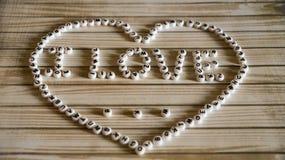 Die Phrase ` I Liebe ` großes Herz bestanden aus weißem, rund, Plastikblöcke auf einer Holzoberfläche Stockfotografie