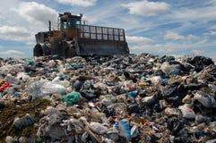 Die Planierraupe auf einem Abfallspeicherauszug lizenzfreie stockfotografie