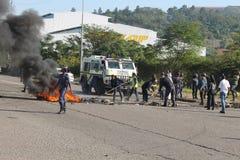 Die Polizei, die nach einer Straße aufräumt, wurde von den Protestierendern in Durban blockiert Stockfotografie