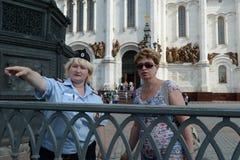 Die Polizeibeamtin zeigt die Richtung des Touristen an Stockbild