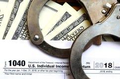 Die Polizeihandschellen liegen auf dem Steuerformular 1040 Das Konzept von proble Lizenzfreie Stockfotografie