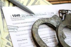 Die Polizeihandschellen liegen auf dem Steuerformular 1040 Das Konzept von proble Stockfotografie