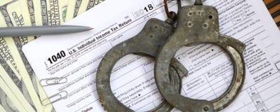 Die Polizeihandschellen liegen auf dem Steuerformular 1040 Das Konzept von proble Lizenzfreie Stockfotos