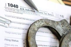 Die Polizeihandschellen liegen auf dem Steuerformular 1040 Das Konzept von proble Stockfoto