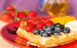 Die populäre Pflegewaffel auf einer roten Platte, mit Früchten Stockfoto