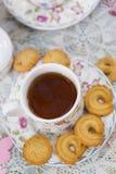 Die Porzellantasse tee und Zuckerplätzchen sind- auf dem Tisch Stockbild