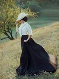 Die Prinzessin in einem Weinlesekleid und -c$tragen eines weißen Hutes mit Federn gehend entlang die Steigungen der Hügel Der Win stockbilder