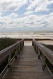 Die Promenade, die zu den Strand an einem bewölkten Tag führt lizenzfreie stockbilder