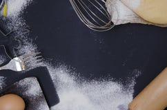 Die Pulverisierung durch Mehl stellte Teig für bakary stics mit hölzernem Nudelholz über schwarzem basground bereit Lizenzfreies Stockfoto
