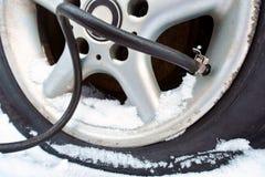 Die Pumpe pumpt Luft in den Reifen im Winter stockfoto