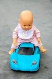 Die Puppe, die auf Spielzeugsportwagen sitzt Lizenzfreies Stockbild