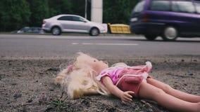 Die Puppe fällt nahe der Straße mit aktivem Verkehr Viele Autos kommen von hinten Langsame Bewegung stock footage