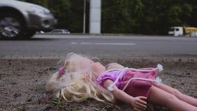 Die Puppe fällt nahe der Straße mit aktivem Verkehr Viele Autos kommen von hinten Langsame Bewegung stock video footage