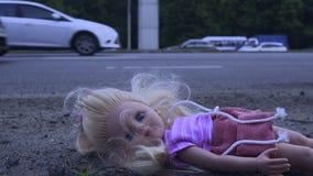 Die Puppe liegt nahe der Straße mit aktivem Verkehr Viele Autos kommen von hinten stock video