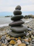 Die Pyramide von sechs Steinen auf dem Strand Lizenzfreie Stockfotografie