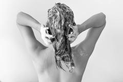Die Rückseite einer Frau, die voll ihr Haar von Seifenlösungen vor a wäscht Lizenzfreie Stockbilder
