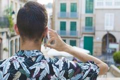 Die Rückseiten des Jungemannes, die auf Mobile sprechen lizenzfreie stockfotografie
