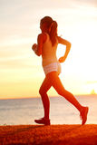 Die rüttelnde Athletenfrau, die bei Sonnensonnenuntergang läuft, setzen auf den Strand lizenzfreies stockbild
