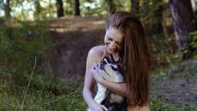 Die recht angemessen-enthäutete junge Frau, die auf Knien sitzt und Hund umarmt, ist glückliche Wanne stock video footage