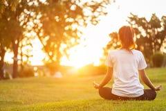 Die recht asiatische Frau, die Yoga tut, trainiert im Park lizenzfreie stockfotos
