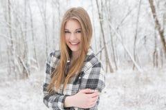 Die recht junge Frau, die in einem Schnee steht, bedeckte Wald Stockbild