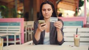 Die recht junge Frau hält die Bankkarte und Smartphone Online-Zahlung Touch Screen herstellend dann lächelnd Internet stock footage