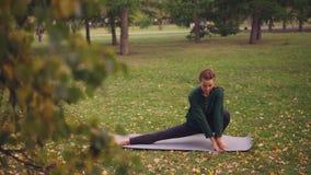 Die recht junge Frau wird auf die Yogapraxis konzentriert, die Beine ausdehnt und auf Yogamatte allein herein ausbildend im Park  stock video