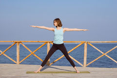 die recht junge Sitzfrau, die Yoga tut, trainiert auf dem Sommerstrand Lizenzfreies Stockbild