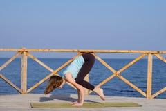 die recht junge Sitzfrau, die Yoga tut, trainiert auf dem Sommerstrand Stockbilder
