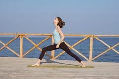 die recht junge Sitzfrau, die Yoga tut, trainiert auf dem Sommerstrand Lizenzfreie Stockfotos