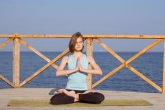 die recht junge Sitzfrau, die Yoga tut, trainiert auf dem Sommerstrand Stockfoto