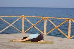 die recht junge Sitzfrau, die Yoga tut, trainiert auf dem Sommerstrand Lizenzfreie Stockbilder