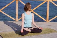 die recht junge Sitzfrau, die Yoga tut, trainiert auf dem Sommerstrand stockbild