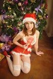 Die recht sexy Frau, die Santa Claus trägt, kleidet und sitzt auf einer warmen Wolldecke Stockbild