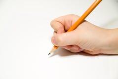 Die rechte Hand des Kindes, die einen Bleistift an über Weiß hält Stockbilder