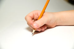 Die rechte Hand des Kindes, die einen Bleistift an über Weiß hält Stockfotografie