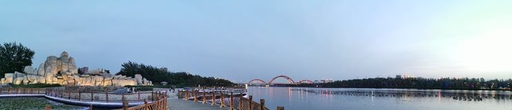 Die Regenbogenbrücke im Abstand, das Holz, der Rockery im Abstand, der See lizenzfreie stockbilder
